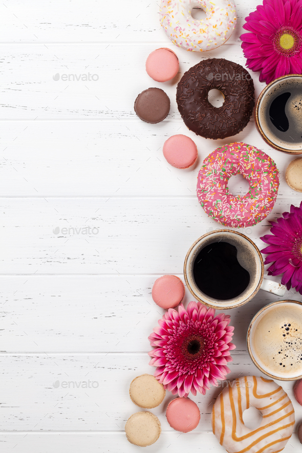 Coffee cups, donuts and gerbera flowers - Stock Photo - Images