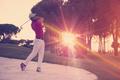 golfer hitting a sand bunker shot on sunset - PhotoDune Item for Sale