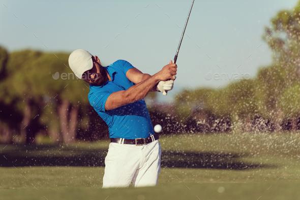 pro golfer hitting a sand bunker shot - Stock Photo - Images