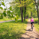Woman cycling a mountain bike in city park, summer day - PhotoDune Item for Sale