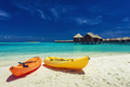 Yellow and orangel kayaks on the tropical beach with villas - PhotoDune Item for Sale