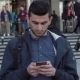 Young Middle Eastern Man Using Smartphone in City as People Are Walking Behind - VideoHive Item for Sale