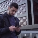 Young Happy Middle Eastern Man Using a Smartphone and Smiling in City - VideoHive Item for Sale