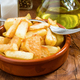 earthenware dish full of chips, with fork, salt and oil - PhotoDune Item for Sale