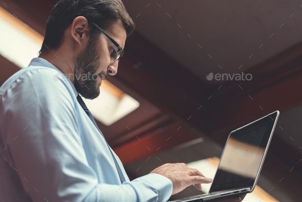 Young businessman with laptop - Stock Photo - Images