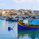 Marsaxlokk fishermen village in Malta. Traditional colorful boats at the port of Marsaxlokk - PhotoDune Item for Sale