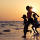 Happy children playing on the beach at the sunset time. - PhotoDune Item for Sale