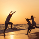 Father son and daughter playing on the beach at the sunset time. - PhotoDune Item for Sale