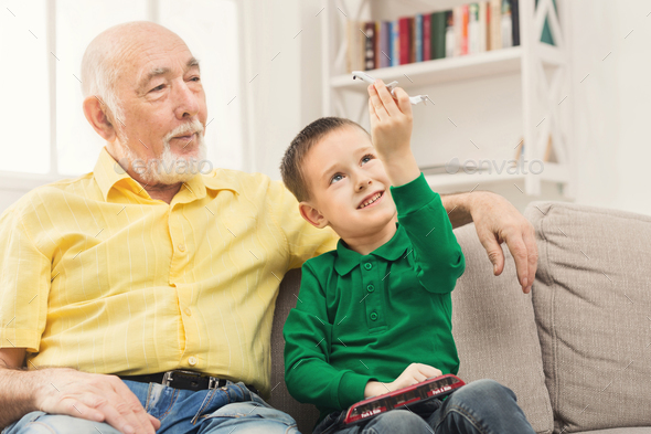 Boy playing with toy pane with his grandfather - Stock Photo - Images
