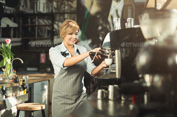 Experienced barista making coffee in professional coffee machine - Stock Photo - Images
