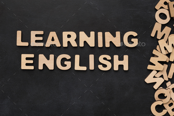 Learning English spelled with wooden letters on black background - Stock Photo - Images