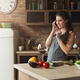 Happy woman talking on phone in the home kitchen - PhotoDune Item for Sale