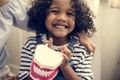 Cheerful young kid holding a dental model - PhotoDune Item for Sale