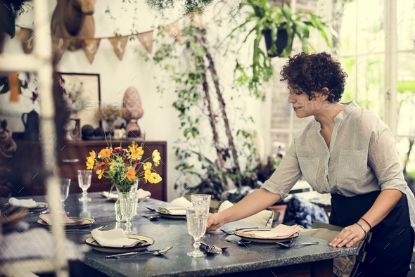 Woman setting a table for the customers - Stock Photo - Images