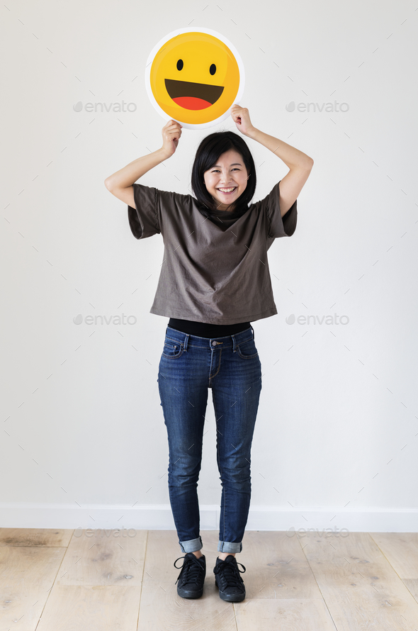 Happy Asian woman holding a smiley emoticon face - Stock Photo - Images