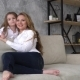 Lovely Mother and Daughter in the Same Clothes Posing Sitting on the Couch - VideoHive Item for Sale