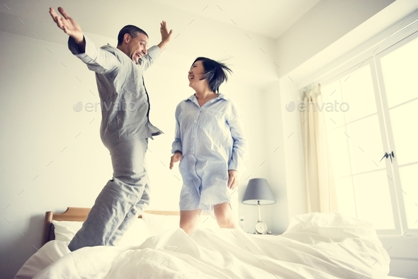 A couple jumping on the bed - Stock Photo - Images