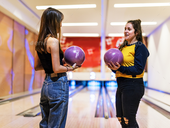 Friends talking at a bowling alley - Stock Photo - Images