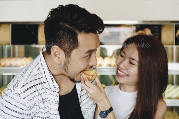 Asian girl feeding her boyfriend - Stock Photo - Images