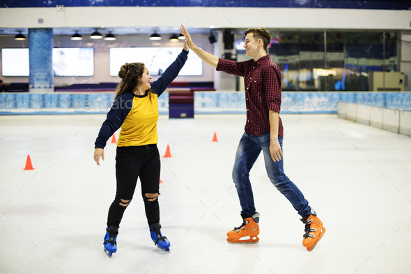 Friends giving each other a high five a they are ice skating on the ice rink - Stock Photo - Images