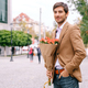 Portrait of young handsome man smiling holding a bunch of roses - PhotoDune Item for Sale