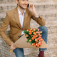 Handsome man holding bouquet of roses talking happy on phone - PhotoDune Item for Sale