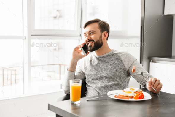 Handsome bachelor 30s wearing casual clothing talking on mobile - Stock Photo - Images