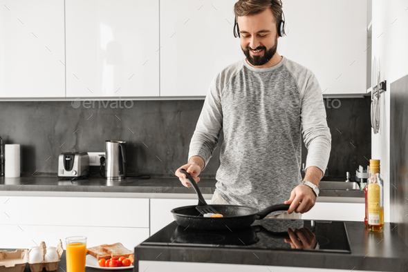 Cheerful man 30s wearing casual clothing frying eggs for breakfa - Stock Photo - Images