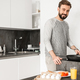 Single happy man wearing casual clothing cooking dinner on fryin - PhotoDune Item for Sale