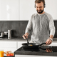 Cheerful man 30s wearing casual clothing frying eggs for breakfa - PhotoDune Item for Sale