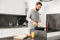 Handsome bachelor with short brown hair and beard cooking omelet - PhotoDune Item for Sale