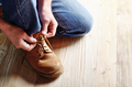 Carpenter in blue jeans tying shoelaces of yellow work boots on - PhotoDune Item for Sale