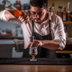 Barman pouring mixture into a jigger - PhotoDune Item for Sale