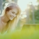 Beautiful Young Woman Enjoys a Laptop. Lies on the Lawn in the Backyard of the House in the Sun at - VideoHive Item for Sale