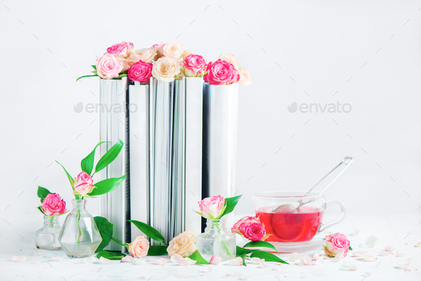 Leisure and reading concept on a white background with copy space  Stack of  white books with a cup