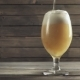 Beer Poured in Glass on Wood Background. Foam Sliding Down Side - VideoHive Item for Sale