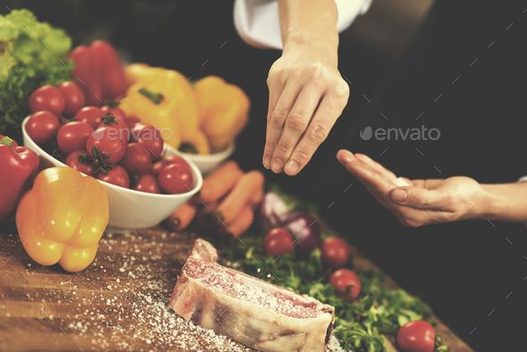 Chef putting salt on juicy slice of raw steak - Stock Photo - Images
