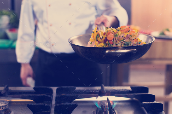 chef flipping vegetables in wok - Stock Photo - Images