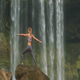 Slim Girl Poses on Round Rock against Waterfall - VideoHive Item for Sale