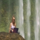 Wind Shakes Hair Girl Works on Notebook by Waterfall - VideoHive Item for Sale