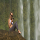 Girl Surfs Internet Sitting on Stone by Waterfall - VideoHive Item for Sale