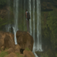 Guy with Backpack Standing on Rock Drinks Water by Waterfall - VideoHive Item for Sale