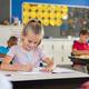 Smiling school girl writing - PhotoDune Item for Sale