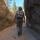 A Hiker Mature Woman Walks Between The Smooth And Wavy Rocks Of The Canyon - VideoHive Item for Sale