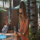 Nice Lady Looks into Mobile against Pool by House - VideoHive Item for Sale