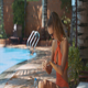 Woman in Bikini Uses Sunscreen for Arms by Pool - VideoHive Item for Sale