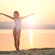 Young woman in strings swimsuit stands on the beach in sunrise - PhotoDune Item for Sale