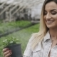 Happy Pretty Girl Spraying Flowerpots in Greenhouse. Slowly - VideoHive Item for Sale