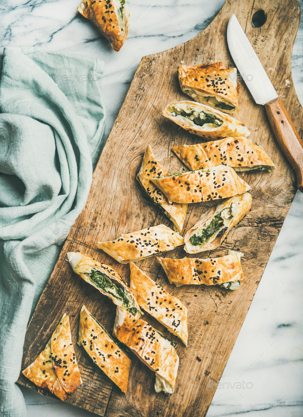 Freshly baked Turkish borek roll cut in slices on board - Stock Photo - Images