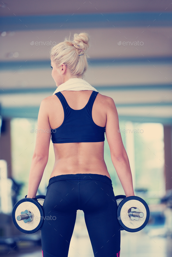 lifting some weights and working on her biceps in a gym - Stock Photo - Images